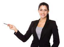 Businesswoman with pen point aside Stock Photography