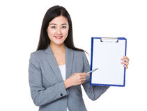 Businesswoman with pen point to blank page of clipboard. Isolated on white background Stock Image