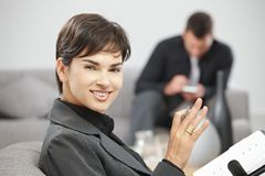 Businesswoman with personal organizer. Happy young businesswoman sitting on sofe at office writing notes to personal organizer, smiling Stock Photos