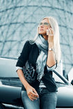 Fashion business woman calling on cell phone by her car Royalty Free Stock Photography