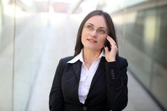 Businesswoman on the phone. A business woman is talking on the phone in front of a corporate building Royalty Free Stock Image