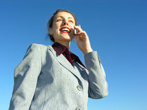 Businesswoman with phone on blue sky. From down view stock images