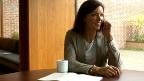 Businesswoman on a phone call in a bar stock footage