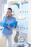 Businesswoman on phone call checking documents. Businesswoman on mobile phone call checking documents in folder, standing at shelf Stock Photo