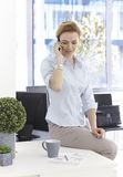 Businesswoman on phone call. Young businesswoman sitting on top of desk, talking on mobilephone, looking at business diagrams Stock Photography