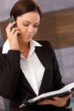 Businesswoman on phone call. Young businesswoman talking on mobilephone, holding organizer Royalty Free Stock Photography