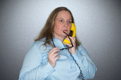Businesswoman on phone calls and is thoughtfully chewing on her glasses Stock Photography