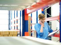 Businesswoman on the phone and checking inventory in warehouse Royalty Free Stock Images
