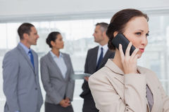 Businesswoman on the phone while colleagues talking together. In bright office Royalty Free Stock Photo