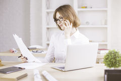 Businesswoman on phone doing paperwork Stock Images