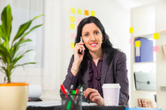 Businesswoman on phone in her office Royalty Free Stock Photography