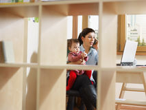 Businesswoman on the phone, holding daughter Royalty Free Stock Photo