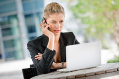 Businesswoman with Phone and Laptop Royalty Free Stock Photography