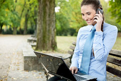 Businesswoman with phone and laptop Royalty Free Stock Photos