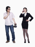 Businesswoman on the phone, man with stationary phone, studio shot Stock Photography