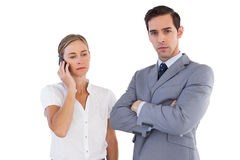 Businesswoman on the phone next to her colleague. On white background Royalty Free Stock Photos