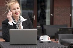 Businesswoman on phone outdoors with laptop and cup of coffee Stock Photos