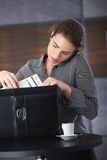 Businesswoman on phone packing briefcase Stock Photo