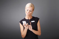 Businesswoman with phone. Portrait of dissatisfied businesswoman holindg in her hand mobile phone and touching the screen Stock Image