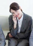 Businesswoman on phone sitting in a waiting room Royalty Free Stock Photo
