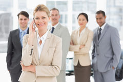 Businesswoman on the phone smiling at camera with team behind her Royalty Free Stock Image