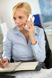 Woman in office talking on the phone Stock Photos