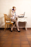 Businesswoman with phone touching screen laptop Stock Photography