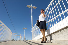 Businesswoman on the phone at train station. Upward view of an attractive looking and smiling mature business woman in her fifties, wearing glasses, white blouse Stock Images