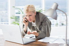 Businesswoman on the phone and using her laptop Royalty Free Stock Photos