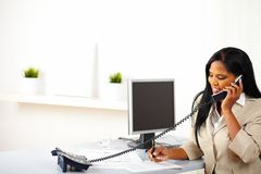 Businesswoman on phone while working Stock Images