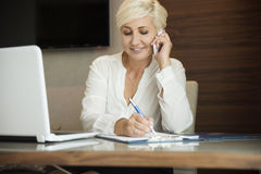 Businesswoman on the phone and writing stock photos