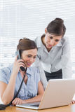 Businesswoman phoning and looking at laptop with colleague Royalty Free Stock Photos