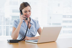 Businesswoman phoning and looking at laptop Royalty Free Stock Photography