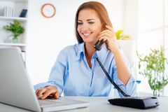 Businesswoman Phoning In The Office. A young beautiful businesswoman sitting in the office, phoning and using laptop Stock Images