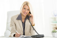 Businesswoman Phoning In The Office. A young blond businesswoman phoning in office and with a smile on her face looking at the camera Stock Images