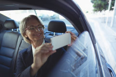Businesswoman photographing in car Stock Photo