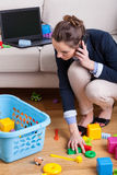 Businesswoman picking up toys Royalty Free Stock Image