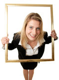 Businesswoman pictureframe wideangle. A wide-angle shot of a young businesswoman looking through a pictureframe Royalty Free Stock Photography