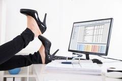 Businesswoman& x27; piede di s sullo scrittorio Fotografie Stock Libere da Diritti