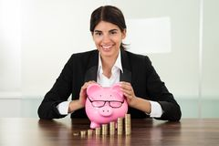 Businesswoman with piggybank and coins stacks Stock Photography