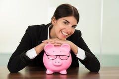 Businesswoman with piggybank at desk Stock Image