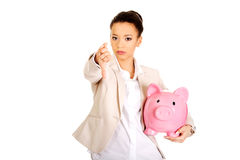 Businesswoman with piggybank and thumbs down. Royalty Free Stock Photos