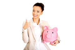 Businesswoman with piggybank and thumbs up. Royalty Free Stock Image