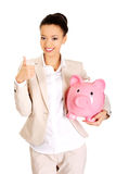 Businesswoman with piggybank and thumbs up. Royalty Free Stock Photo