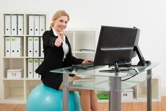 Businesswoman On Pilates Ball While Using Computer Royalty Free Stock Photography