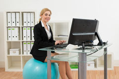 Businesswoman On Pilates Ball While Using Computer Stock Images