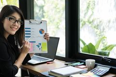 Businesswoman plan new business project at workplace. woman show. S market data report at office. Young finance analyst work with financial graph & chart diagram stock photo