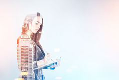 Businesswoman with a planner, blurred city. Portrait of a beautiful young businesswoman wearing a black suit and holding a planner and a pen taking notes Royalty Free Stock Images
