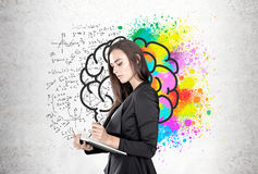 Businesswoman with a planner, brain formulas. Portrait of a beautiful young businesswoman wearing a black suit and holding a planner and a pen taking notes Stock Image