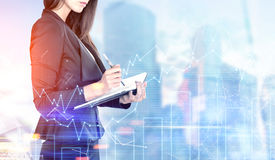 Businesswoman with a planner, graphs in a city. Portrait of a beautiful young businesswoman wearing a black suit and holding a planner and a pen taking notes Royalty Free Stock Images